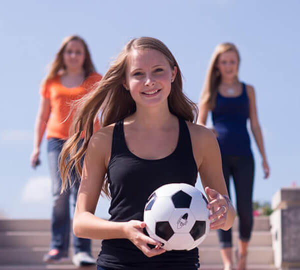 Girl in foreground with soccerball
