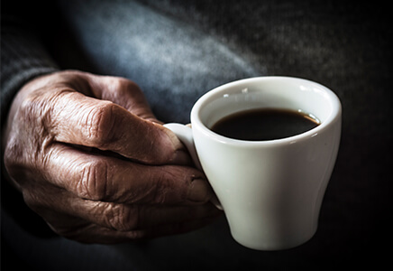 Older hand holding cup of coffee
